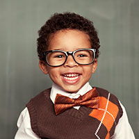 Young child smiling with bowtie and glasses.