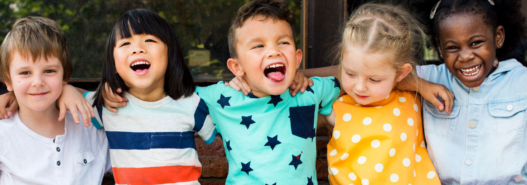 Children smiling and laughing sitting on a brick wall outside in colorful clothing.