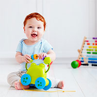 Infant smiling holding a toy.