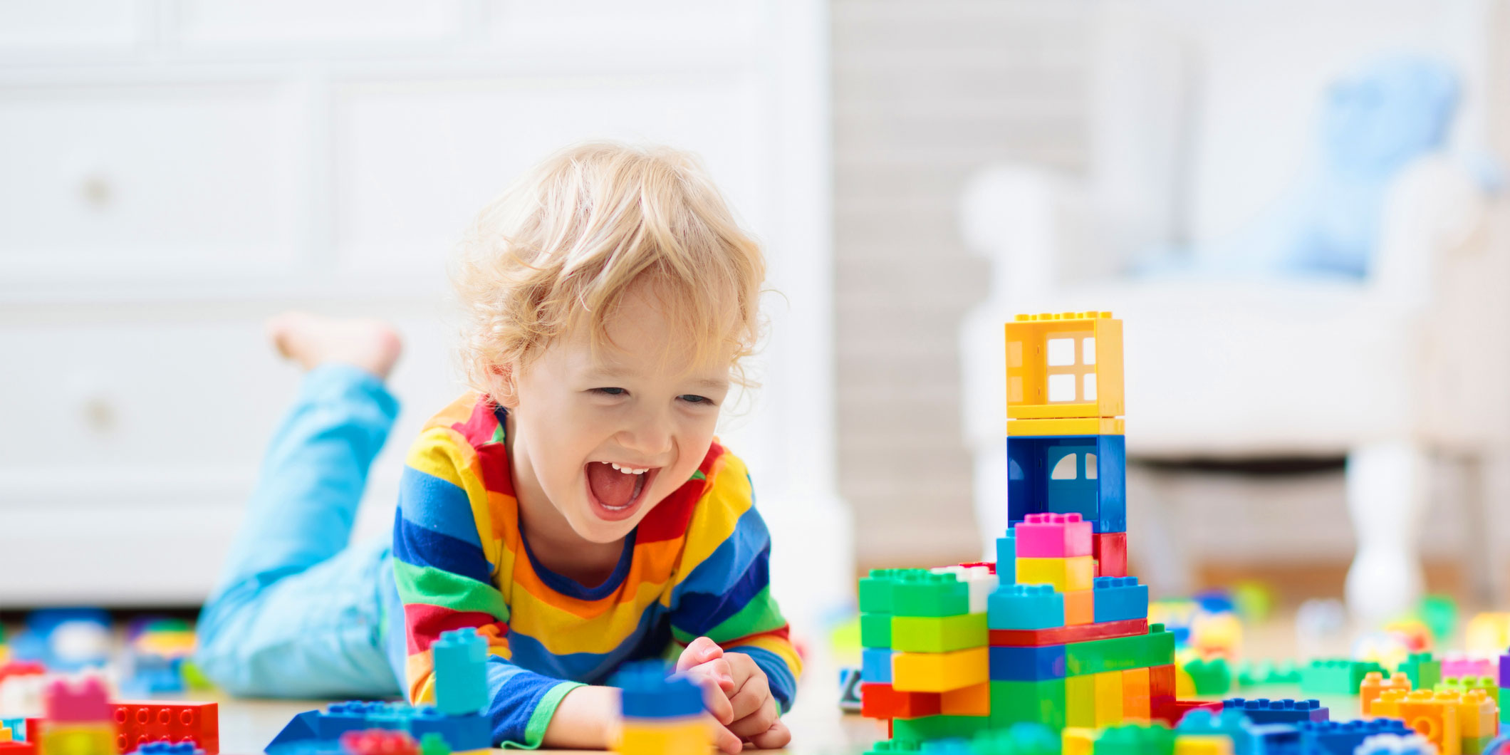 Young child smiling and laughing on the floor with colorful building blocks.