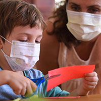 Young student with teacher in masks cutting paper with scissors for a craft.